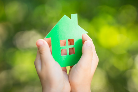 Little paper house in children s hands against green spring Stock Photo