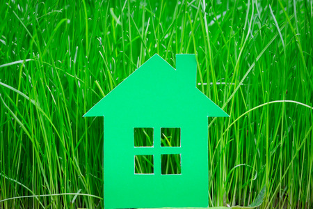 Green paper house on spring grass photo