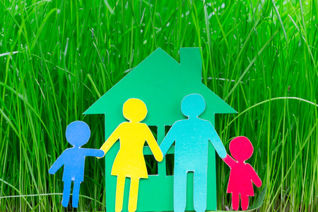 child protection: Paper family and house on spring green grass  Ecology concept