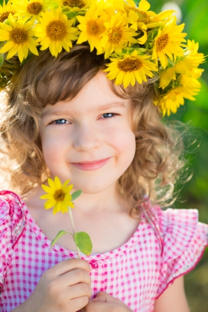 Beautiful child in wreath of spring sunflower photo