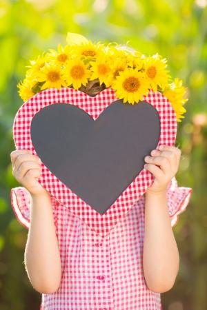 Child holding blackboard blank in heart shape outdoors photo