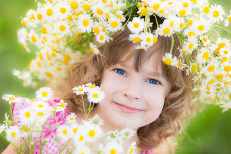 Happy child in wreath of flowers outdoors in spring park photo
