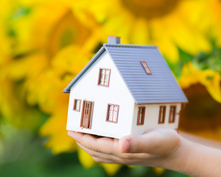 House in children s hands against spring flowers background