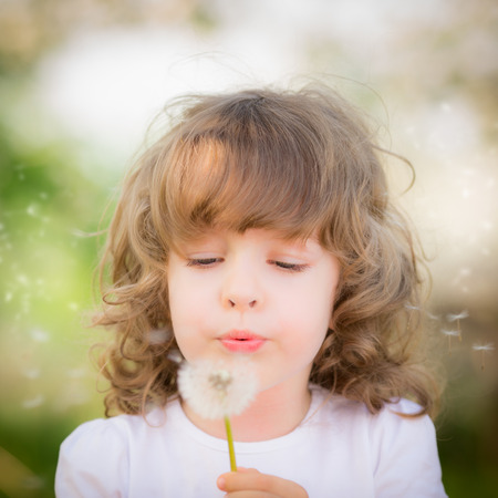 Happy child blowing dandelion outdoors in spring park photo