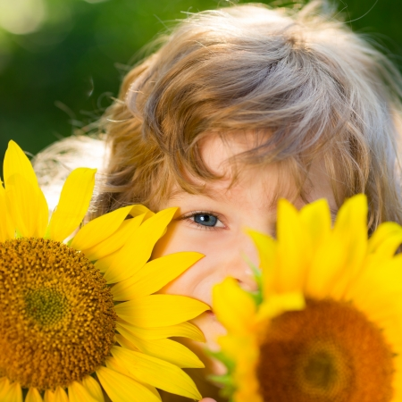Happy child playing with sunflowers outdoors in spring park photo