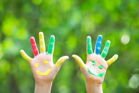 kids painted hands: Smiley hands against green spring