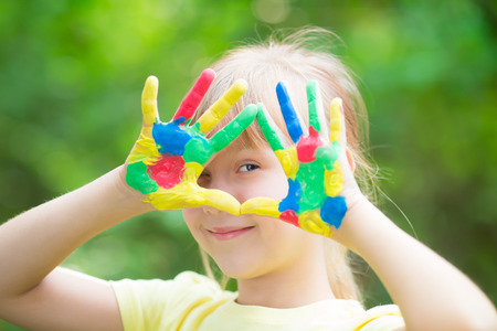 kids painted hands: Child with painted hands against green spring