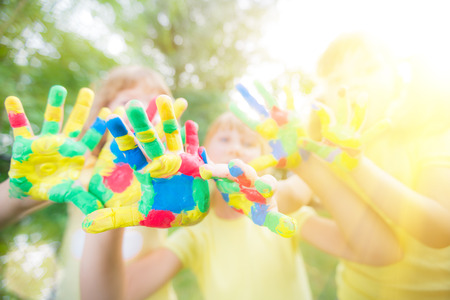 Group of friends with painted hands against green spring  Stock Photo