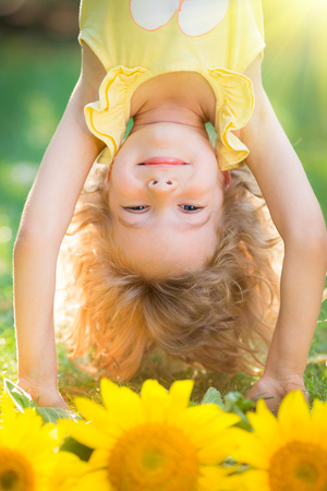 Happy child playing upside down in spring park photo