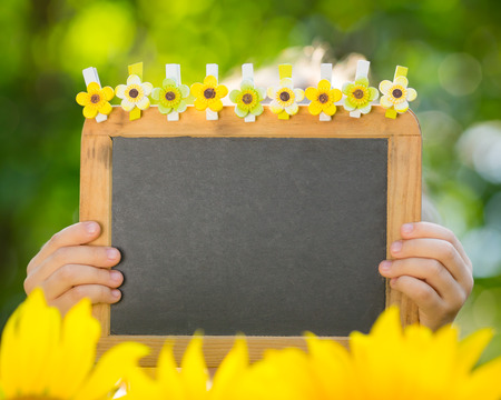 Blackboard blank in children hands outdoors photo