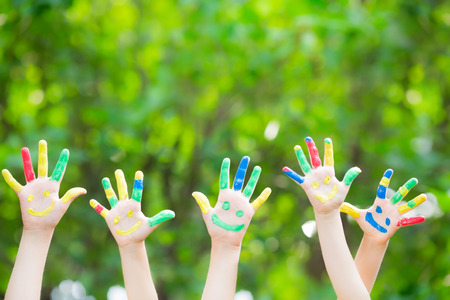 schoolchild: Groep van smiley handen tegen groene lente