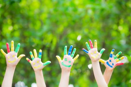 ni�os dibujando: Grupo de manos sonrientes contra verde primavera Foto de archivo