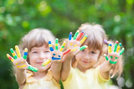 caritas pintadas: Los niños con las manos sonrientes en contra de la primavera verde Foto de archivo