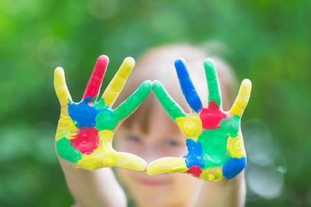 Child with painted hands against green spring  photo