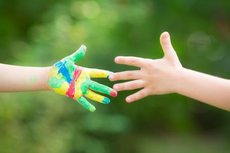 Handdruk met geschilderde handen tegen de groene voorjaar Stockfoto