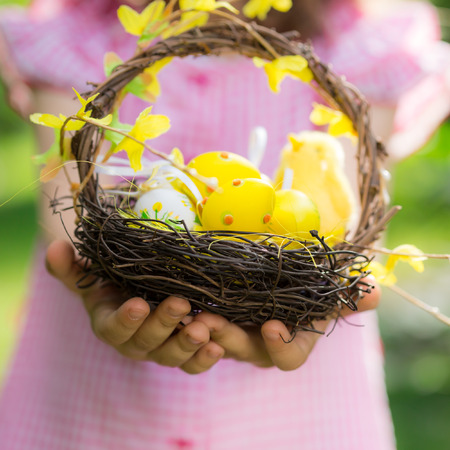 kids holding hands: Easter eggs on green grass. Spring holidays concept