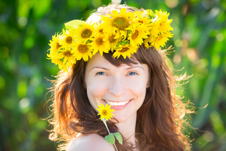 Beautiful woman in wreath of spring sunflower photo