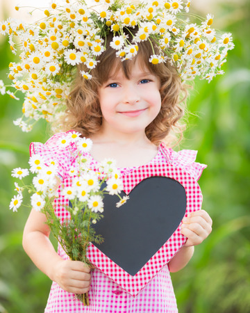 Happy child in wreath of flowers outdoors in spring park Stock Photo