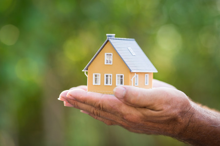 Ecology house in hands against spring blurred background Stock Photo