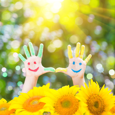 green smiley face: Happy child with smiley on hands against green spring background