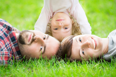 Happy family lying on green grass outdoors in spring park photo