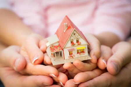 손에 집을 들고 가족. 부동산 개념 스톡 콘텐츠
