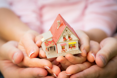 Family holding house in hands. Real estate concept photo