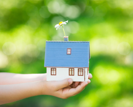 Little house in hands outdoors photo