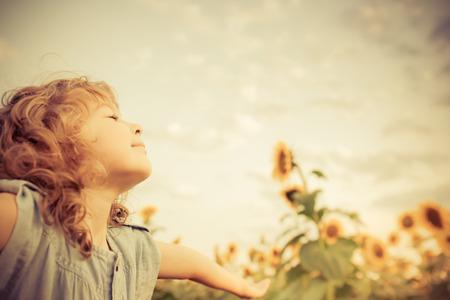 libertad: Ni�o feliz en el campo de girasol. Concepto de la libertad Foto de archivo