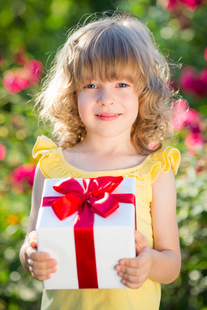 Child holding gift box against green background. Spring family holiday concept. Mother`s day photo