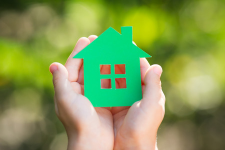 Child holding paper house in hands against spring green background photo