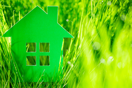 Green paper house in spring grass. Real estate concept photo