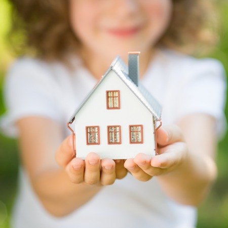 Child holding house in hands outdoors photo