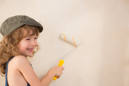 Kid painting wall. Renovation concept photo