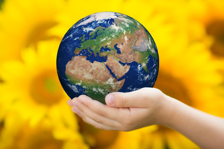 Child holding Earth in hands against sunflower background  Elements of this image furnished by NASA photo