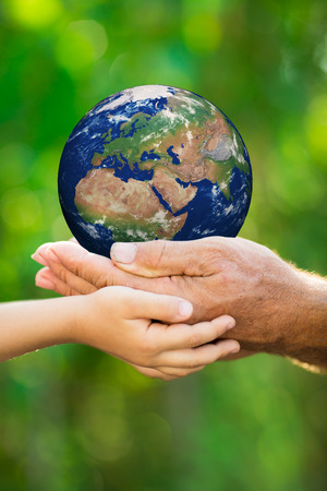 Child and senior man holding Earth in hands against green spring background  Elements of this image furnished by NASA photo