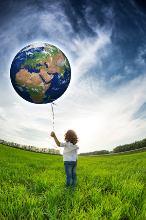 Child holding Earth in hand against blue sky and spring green field  Elements of this image furnished by NASA Banco de Imagens