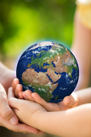 Children holding Earth in hands against green spring background. Elements of this image furnished by NASA photo