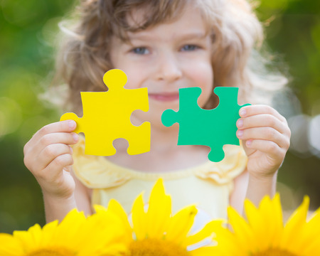 Child holding puzzles in hands against spring green background. Teamwork and partnership concept photo