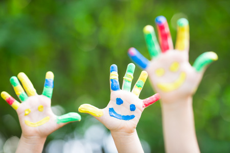 Happy smiley hands against green spring background photo