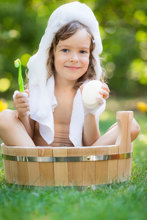Happy child bathing outdoors on green grass in spring garden photo