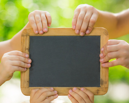 Many hands holding blackboard blank against spring green background photo