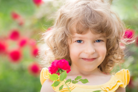 Happy child with rose flower outdoors in spring garden photo