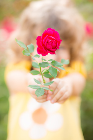Happy child with rose flower outdoors in spring garden. Shallow depth of field photo
