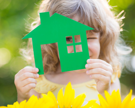 Paper house in hand against spring green background. Real estate concept Stock Photo