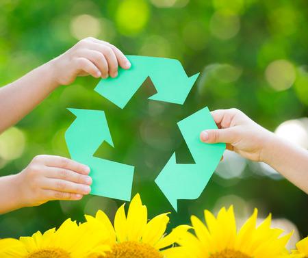 Papier recycle teken in handen tegen groene lente achtergrond. Earth Day concept Stockfoto