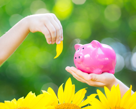 Piggybank and leaf in hands against green spring background. Shallow depth of field