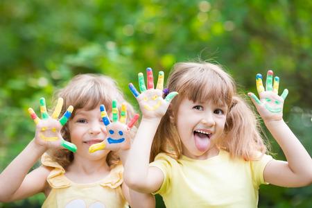 Gelukkig kind met smiley op handen tegen de groene voorjaar achtergrond Stockfoto