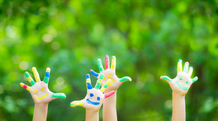handprint: Happy child with smiley on hands against green spring background