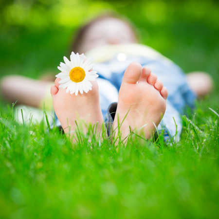 Child lying on grass outdoors in spring park photo